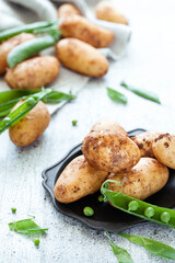 New season raw potatoes with green peas on white wooden background
