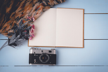 Flat lay open blank notebook, old camera on white wooden table
