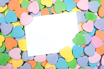 Blank card in heart shaped candy pile