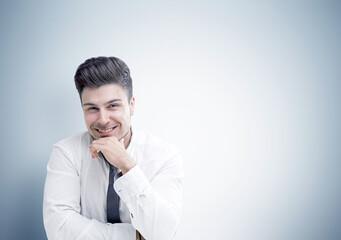 Cheerful businessman sitting near gray wall
