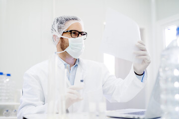 Lab technician doing water analysis, dressed in protective sterile equipment. Paper production.