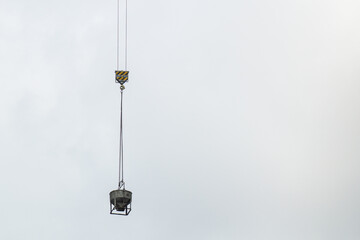 A bucket of concrete hanging in the sky for building construction