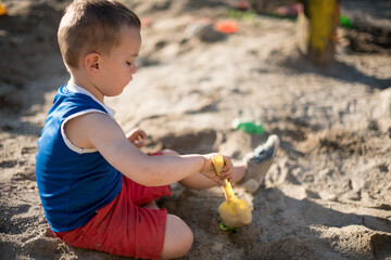 Little cute boy playing with a sand.