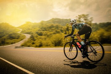 Women cycling mountain road bike in the morning Wall mural