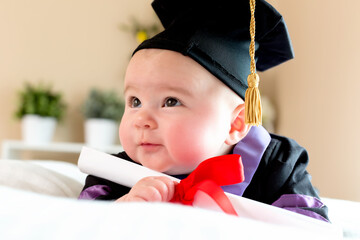 Baby girl in graduation cap and gown