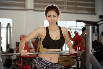 Happy Asian Woman With Barbells In The Gym.