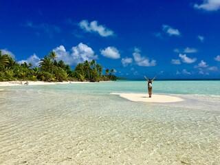 Beautiful young lady standing on a small sandbank in the turquoise lagoon of Marlon Brando's atoll Tetiaroa, Tahiti, French Polynesia