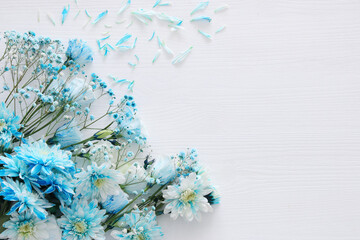 beautiful and delicate blue flowers arrangement on white wooden background