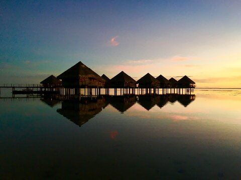 Beautiful view on Moorea and the overwater bungalows of a luxury resort during sunset at the beach of Punaauia