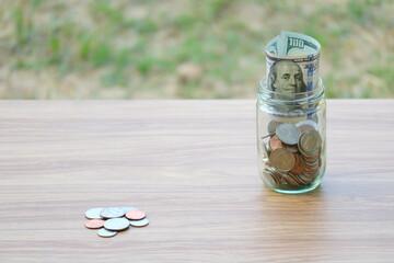 Dollar coin and banknote cash saving in glass jar, finance saving concept