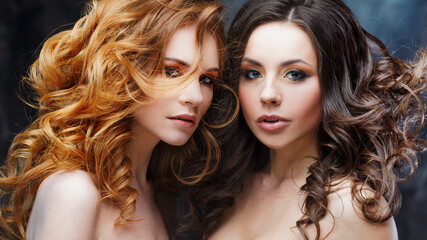 Two charming beauties with luxurious curly hair. Brunette and redhead. Studio portrait on the dark background.