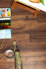 Painter's workplace. Watercolor paint and brushes on table top view. Drawing lessons, art school, young artist concept