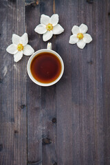 White anime flowers with a cup of tea on a wooden background