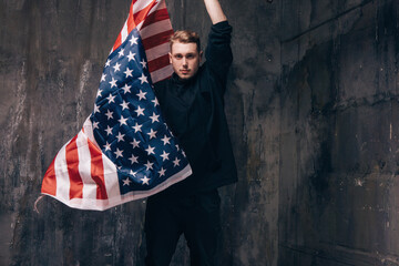 Young USA patriot with flying national flag. Strong man in black cloth on dark studio background. Independence day, confidence, pride, fidelity to the nation, memorial day concept