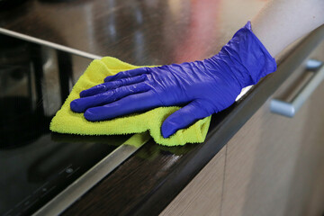 Closeup on woman's hands in blue protective rubber gloves cleaning kitchen cabinets