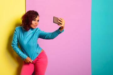 Fashion pretty woman makes self portrait on smartphone in blue jacket