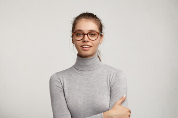 People and lifestyle. Close up indoor shot of attractive confident young Caucasian female with pretty features wearing trendy eyeglasses smiling, keeping hands folded, posing at grey blank studio wall