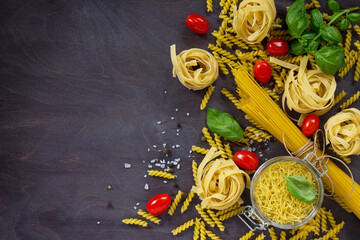 Ingredients for the preparation of Italian pasta - spaghetti, fusilli, fettuccine, basil, cherry tomato and pepper. Top view with space for text.