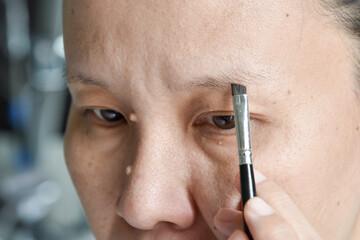 asian woman applying makeup with eyebrow brush