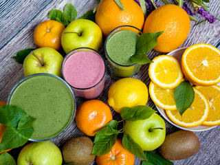 A lot of ripe juicy fruit and three glasses of smoothies on a wooden table