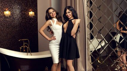 Fashion portrait of two happy young woman wearing white and black halter dresses and posing in luxury interior.