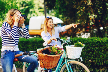 Two young women tourists exploring the city on bicycles and taking photos