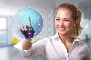 junge Frau mit holografischem Globus vor modernem Büro