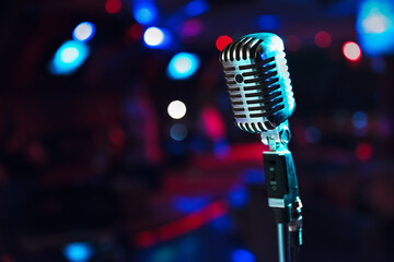 Retro microphone against blur colorful light background