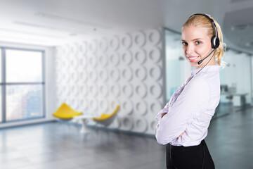 junge lächelnde Geschäftsfrau mit Headset vor modernem Bürohintergrund