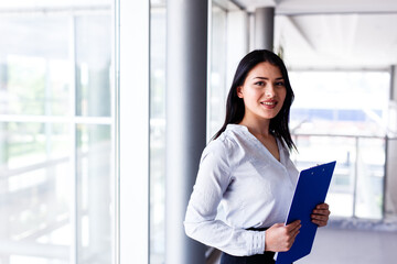 Attractive woman standing in business building with paper board in her hands