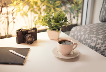 coffee cup, Retro camera, notebook, white pen and green Plastic plants on white table in the coffeeshop with sun's rays in the morning