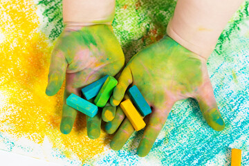 Baby's hands with colorful pastel chalks. Children's Creativity. Early child development