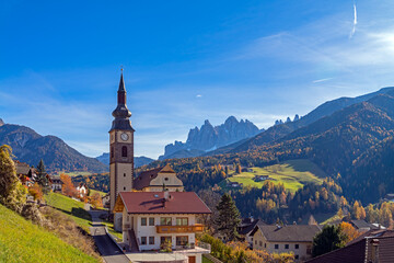Italy. Dolomites. Autumn landscape with bright colors, house and larch trees in the sunlight.