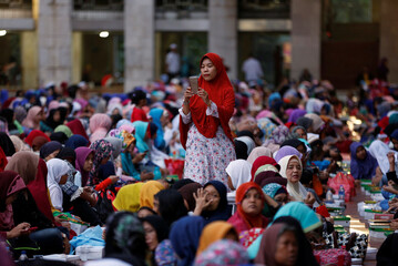 A woman takes a picture of women and children waiting to break fast at Istiqlal Mosque during the holy month of Ramadan in Jakarta