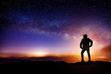 Silhouette a person is standing on mountains with Milky Way galaxy.