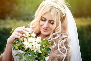 Beautiful young bride's wedding happy together in a park in white dress with veil and fur coat hugging a wedding bouquet, young family, looking lovingly