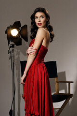 Young pretty beautiful woman in red long evening dress with makeup, red lips and classical hollywood waves hairstylestanding at film set with two cinema lights.