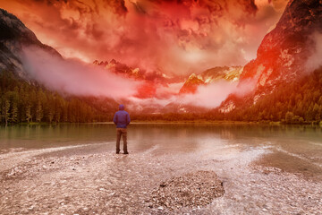 traveler looks at the dawn in the mountains by the lake