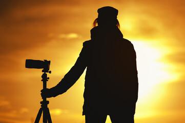 Silhouette of Female photographer against sunset