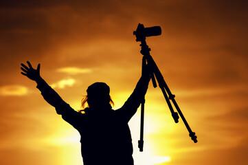 Female photographer silhouette at setting sun