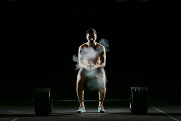 Fitness training. Man doing exercises or training with barbell in dark gym.
