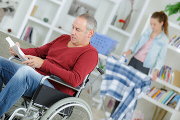 Man in wheelchair reading book, carer ironing in background