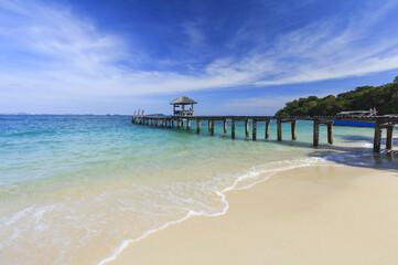 Wood bridge pier on summer tropical sea in blue sky.