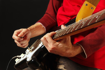 Posing hands of musician playing the electric guitar on the black background