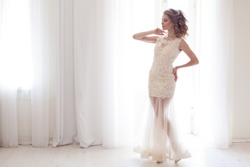 bride in a beautiful wedding dress stands in a white room