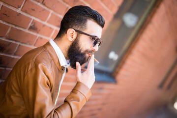 Brutal caucasian hipster smoking cigar on brick wall outdoor