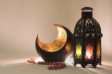 Lantern and a copper crescent in a low light, used as a greeting card for ramadan month or religious celebration