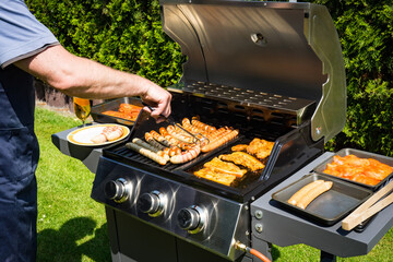 Photo sur Aluminium Grill, Barbecue Grillsaison - Mann beim grillen am Gasgrill
