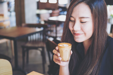 A beautiful Asian woman holding and drinking hot coffee with feeling good in vintage cafe