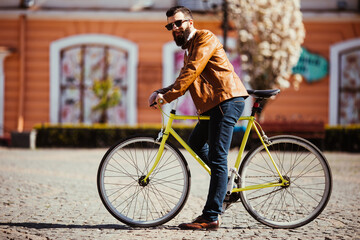 Handsome young bearded man in sunglasses ride his bicycle on sunny city street